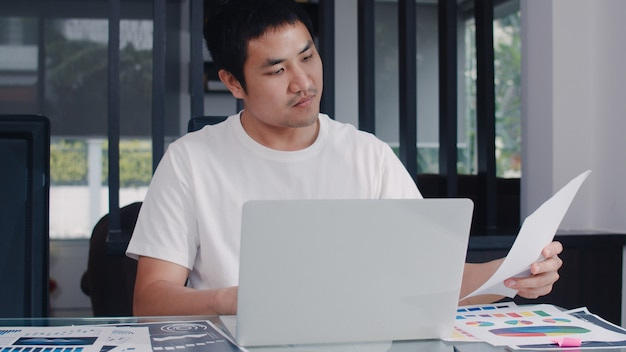 Young asian business man records of income and expenses at home. male worried, serious, stress while using laptop record budget, tax, financial document working in living room at home . Free Photo