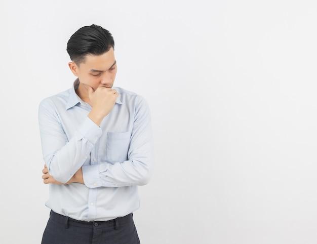 若いアジアビジネス男不幸と何かに不満。白い壁に分離された否定的な表情 Premium写真
