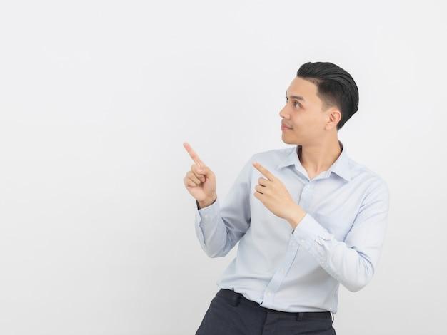 製品や白い背景で隔離のアイデアを提示する手で側を指している青いシャツの若いアジアビジネス男 Premium写真