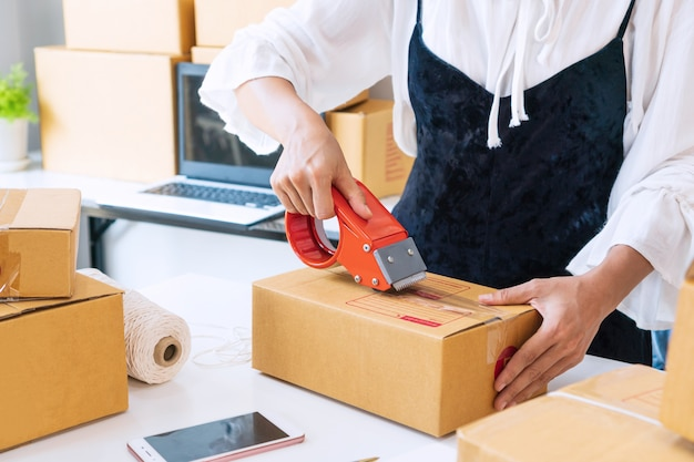 Young asian business owner sealing a box with tape on table. preparing for shipping, packing, online, selling, e-commerce, wotk at / from home concept. close up. Premium Photo
