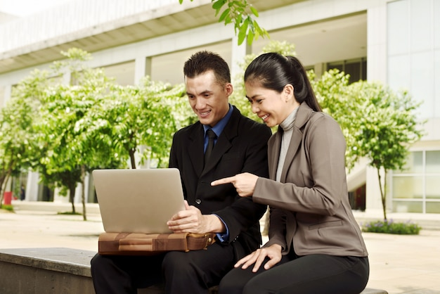 Young asian business people discussing work with laptop Premium Photo