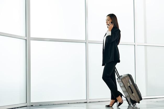 荷物のトロリーバッグ、電話で話していると笑顔で空港で若いアジアビジネス女性。 Premium写真