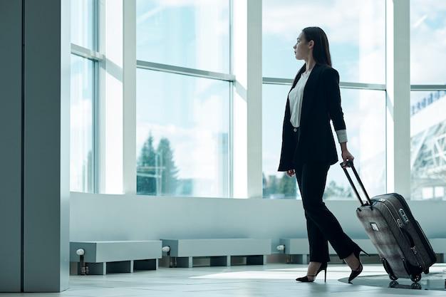 出発を待っている荷物のトロリーバッグが付いている空港で若いアジアビジネス女性 Premium写真