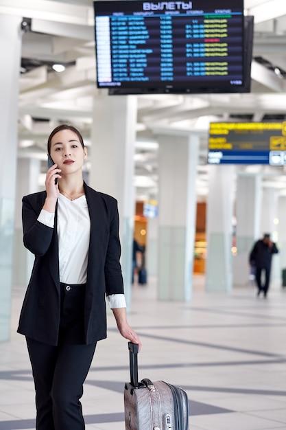 電話で話していると笑みを浮かべて、トロリーバッグが付いている空港で若いアジアビジネス女性。 Premium写真