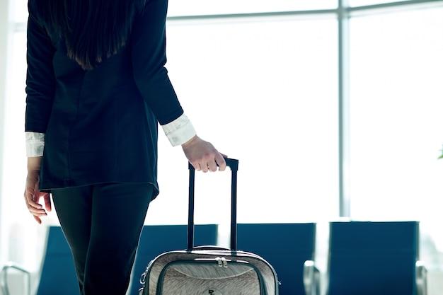 トロリーバッグと空港で出発を待っている若いアジアビジネス女性 Premium写真