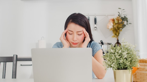 Young asian business woman records of income and expenses at home. lady worried, serious, stress while using laptop record budget, tax, financial document working in modern kitchen at house . Free Photo