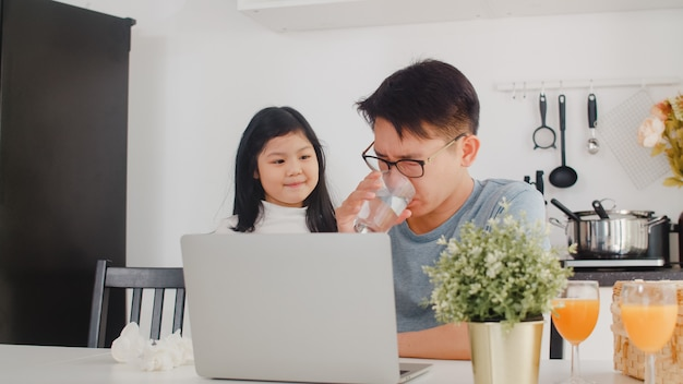 Young asian businessman serious, stress, tired and sick while working on laptop at home. young daughter consoling her father who working hard in modern kitchen at house in the morning . Free Photo