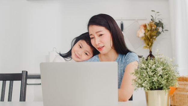 Young asian businesswoman serious, stress, tired and sick while working on laptop at home. young daughter consoling her mother who working hard in modern kitchen at house in the morning . Free Photo