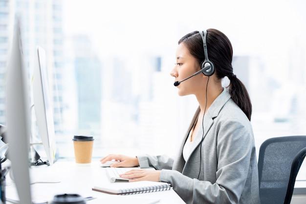 Шлемофоны молодой азиатской коммерсантки нося работая в офисе города центра телефонного обслуживания как оператор телемаркетинга Premium Фотографии