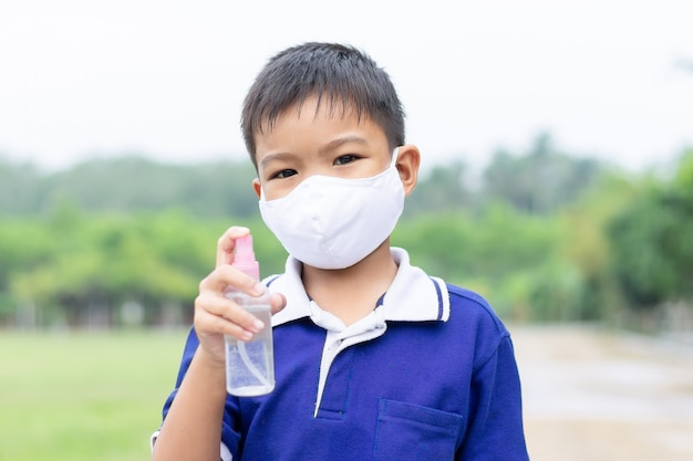 Young asian child boy wearing fabric mask and holding alcohol spray bottle in his hand for prevent coronavirus or covid-19 disease. Premium Photo