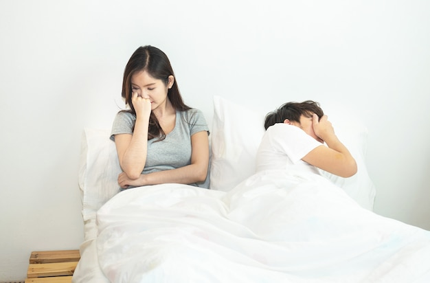Young asian couple in bed having problems and crisis man and woman hands cover head with confused Premium Photo