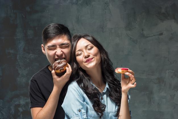 Молодая азиатская пара наслаждается едой сладкого красочного пончика на сером фоне студии Бесплатные Фотографии