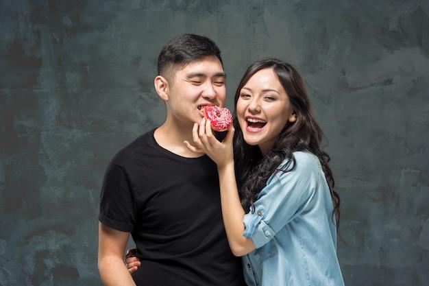 若いアジアのカップルは灰色のスタジオで甘いカラフルなドーナツを食べることを楽しむ 無料写真