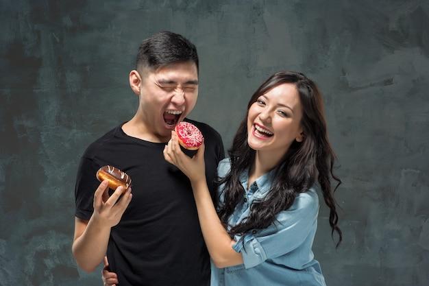 若いアジアのカップルは甘いカラフルなドーナツを食べることを楽しむ 無料写真