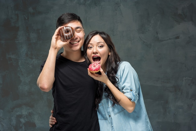 Young asian couple enjoy eating of sweet colorful donut Free Photo