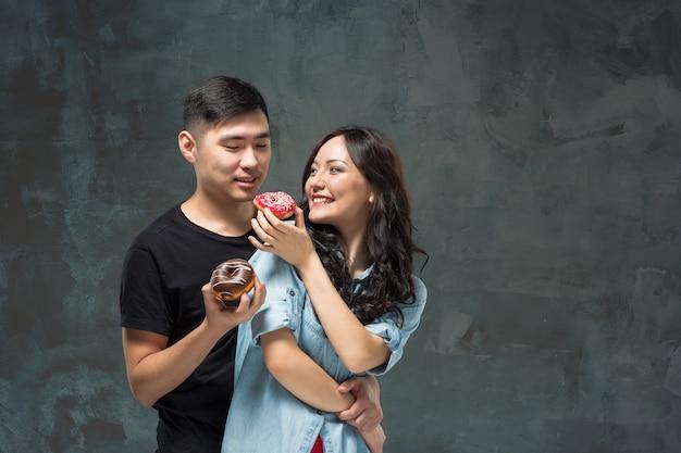 Le giovani coppie asiatiche godono del cibo della ciambella variopinta dolce Foto Gratuite