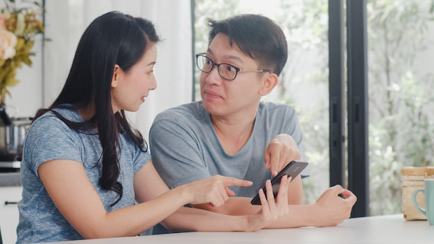 Young asian couple enjoy shopping online on mobile phone at home. lifestyle young husband and wife happy buy ecommerce after have breakfast in modern kitchen at house in the morning . Free Photo