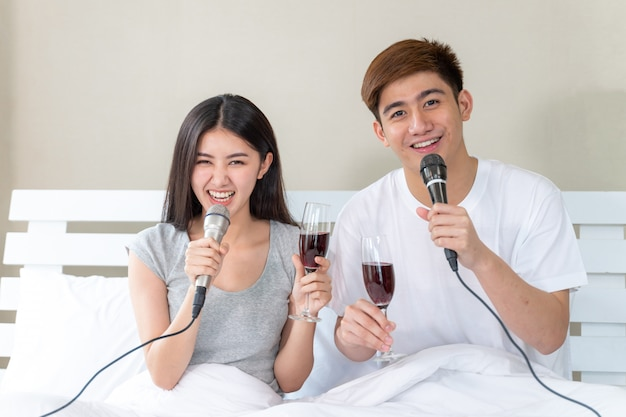 Young asian couple fill happy holding glass of wine and sing a song karaoke party celebrate in the bedroom Free Photo