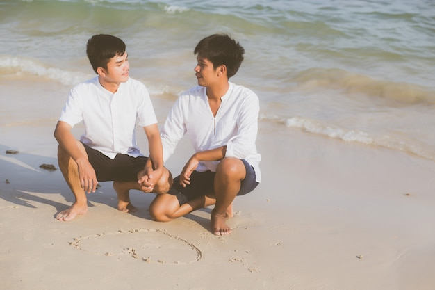 Young asian couple gay drawing heart shape together. Premium Photo
