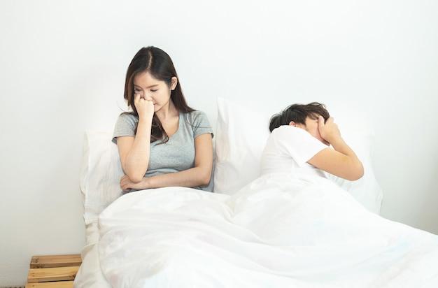 問題と危機の男性と女性の手で混乱しているベッドで若いアジアカップル Premium写真