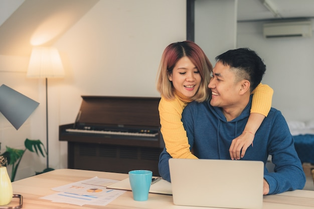Young asian couple managing finances, reviewing their bank accounts using laptop computer Free Photo