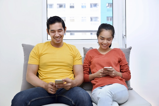Young asian couple relaxing together with using mobile phone Premium Photo