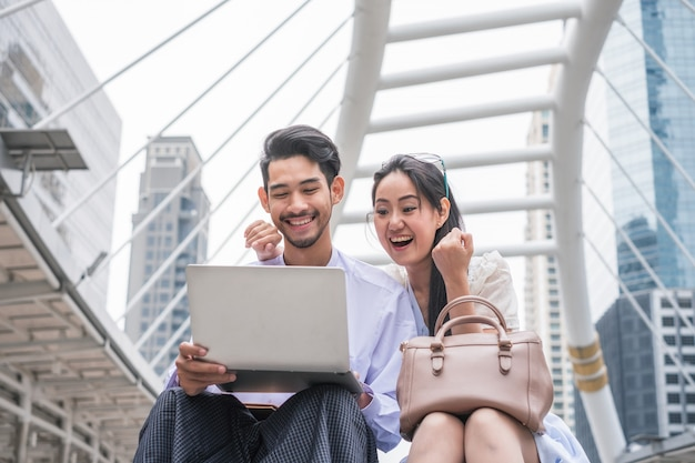 Young asian couple sit using laptop with excited and cheerful Premium Photo