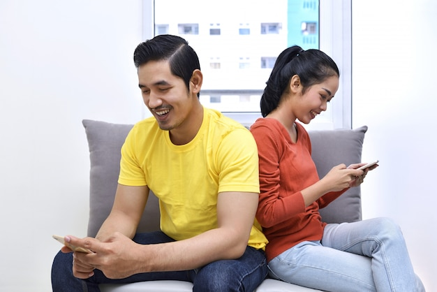 Young asian couple sitting on the sofa with mobile phone Premium Photo