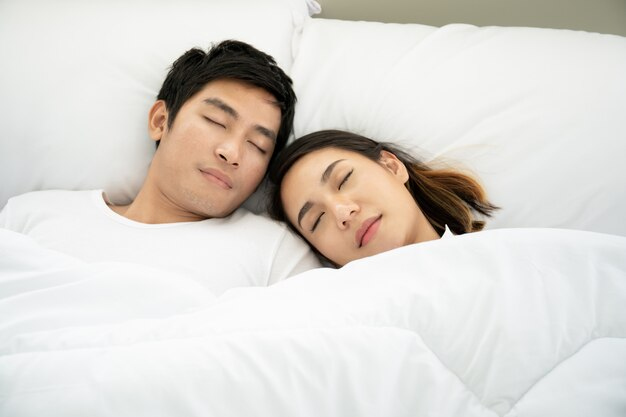 Premium Photo   Young asian couple sleeping on the white bed together close  up.