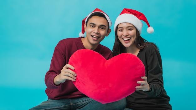 サンタクロースの帽子をかぶって赤いハートを持っている若いアジアのカップル Premium写真