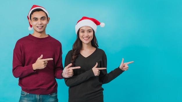 サンタクロースの帽子をかぶって指さしている若いアジアのカップル Premium写真