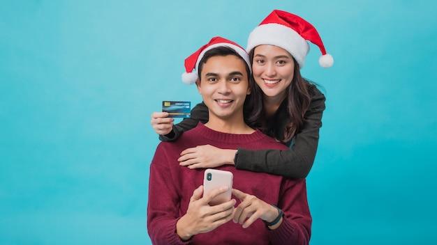 サンタクロースの帽子をかぶって、クレジットカードとスマートフォンでオンラインショッピングをする若いアジアのカップル Premium写真