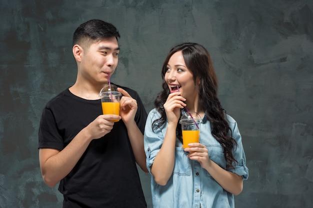 Молодая азиатская пара с бокалами апельсинового сока Бесплатные Фотографии