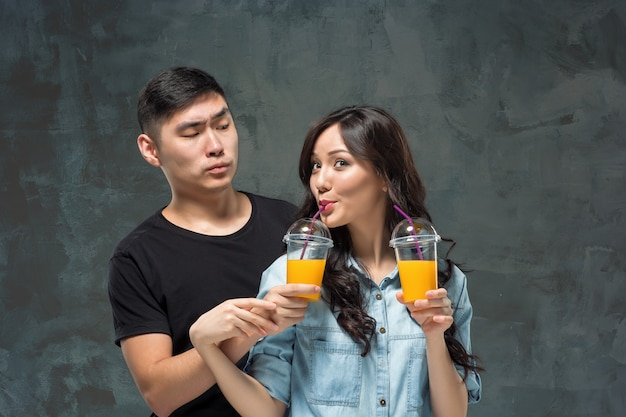 Una giovane coppia asiatica con un bicchiere di succo d'arancia Foto Gratuite