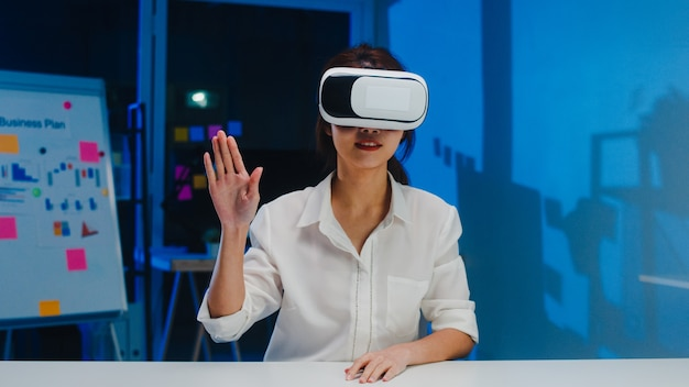 Young asian designer female using vr glasses (virtual reality) testing mobile app from develop software at modern creative home office night. social distancing, quarantine for corona virus prevention. Free Photo