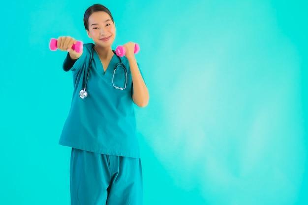 Молодой азиатский доктор женщина упражнения с гантелями Бесплатные Фотографии