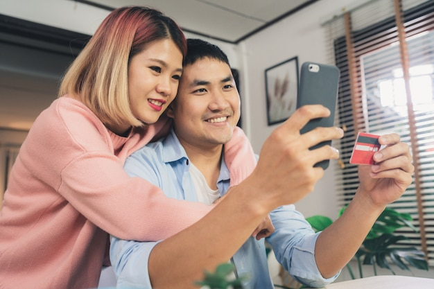 Young asian family couple using smartphone discussing news Free Photo