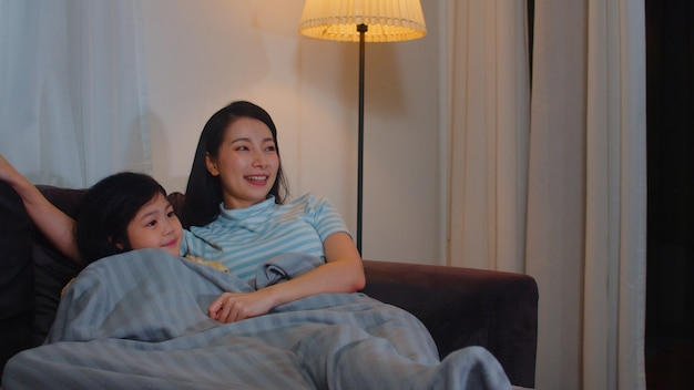 Young asian family and daughter watching tv at home in night. korean mother with little girl happy using family time relax lying on sofa in living room. funny mom and lovely child are having fun. Free Photo