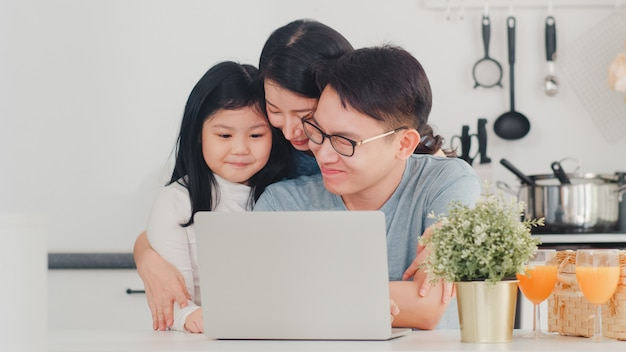 Young asian family enjoy using laptop together at home. lifestyle young husband, wife, and daughter happy hug and play after have breakfast in modern kitchen at house in the morning . Free Photo