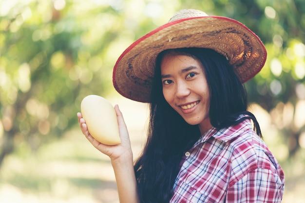 Young asian farmer picking mango fruit in organic farm Premium Photo