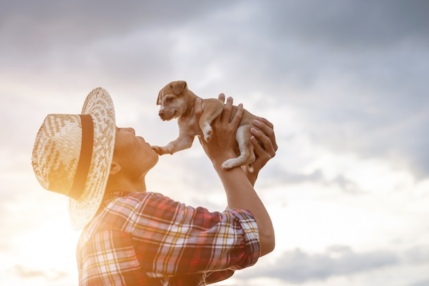 Young asian farmer playing with his brown small pup in the evening after work Premium Photo