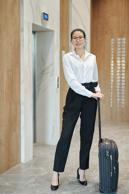 Young asian female business traveler with suitcase standing by elevator door while going to booked hotel room Premium Photo
