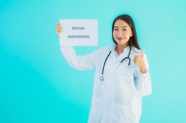社会的距離のサイン紙と若いアジア女性医師 無料写真