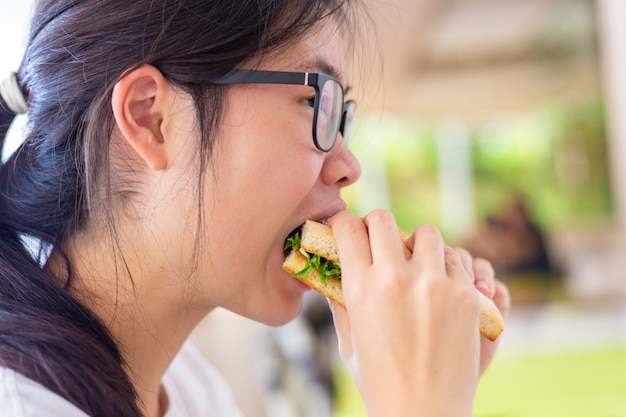 Young asian female holding her salmon sandwich while eating deliciously Premium Photo