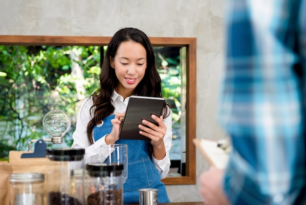 Young asian female staff taking order from customer in coffee shop Premium Photo
