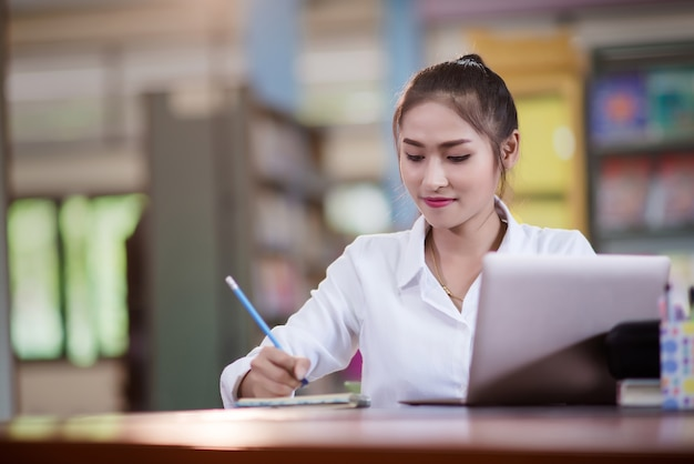 Young asian female student sitting at table and writing on notebook. Premium Photo