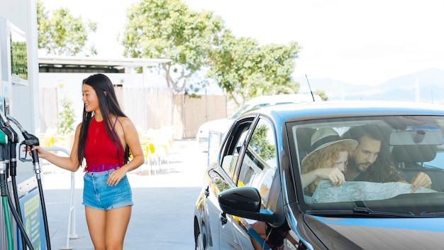 Young asian female taking fuel pump nozzle while friends exploring map Free Photo
