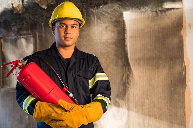 若いアジアの消防士、消防士は建物で燃えている消火を使用します。 Premium写真