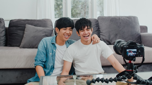 Young asian gay couple influencer couple vlog at home. teen korean lgbtq+ men happy relax fun using camera record vlog video upload in social media while lying sofa in living room at house . Free Photo