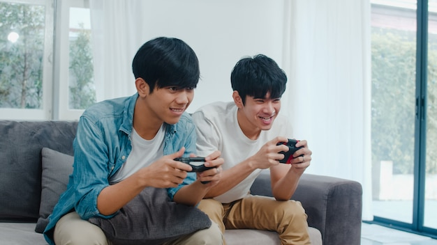 Young asian gay couple play games at home, teen korean lgbtq+ men using joystick having funny happy moment together on sofa in living room at house. Free Photo